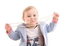 Scherzi con i branelli della perla in sue mani Fotografia Stock