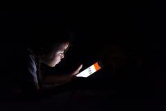 Scherzi con la compressa che si siede sul letto e sui fumetti di sorveglianza alla notte Fotografie Stock Libere da Diritti