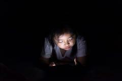 Scherzi con la compressa che si siede sul letto e sui fumetti di sorveglianza alla notte Fotografia Stock Libera da Diritti