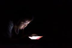 Scherzi con la compressa che si siede sul letto e sui fumetti di sorveglianza alla notte Fotografie Stock