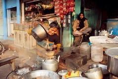 Scherzi contribuire a versare il tè-masala in un caffè del bordo della strada sulla povera via indiana Immagine Stock