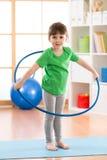 Scherzi fare della ragazza relativo alla ginnastica con il cerchio nella stanza di bambini a casa Fotografia Stock