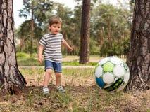 Scherzi giocar a calcioe il calcio al campo del parco della città dell'erba che esegue e che dà dei calci alla palla eccitata nel fotografia stock