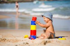 Scherzi i giochi con i giocattoli alla spiaggia nell'estate Fotografia Stock Libera da Diritti