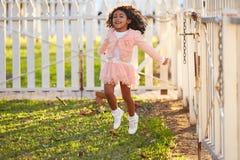 Scherzi il bambino della ragazza che gioca il salto nel parco all'aperto Immagini Stock Libere da Diritti