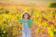 Scherzi il funzionamento della ragazza dell'agricoltore nel campo della vigna in autunno Fotografie Stock Libere da Diritti