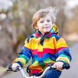 Scherzi il ragazzo in casco di sicurezza e bici variopinta di guida dell'impermeabile Immagini Stock