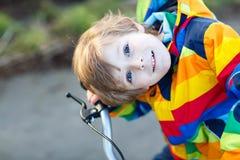 Scherzi il ragazzo in casco di sicurezza e bici variopinta di guida dell'impermeabile, outd Fotografie Stock Libere da Diritti