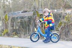 Scherzi il ragazzo in casco di sicurezza e bici variopinta di guida dell'impermeabile, outd Immagini Stock Libere da Diritti