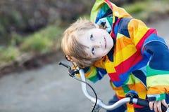 Scherzi il ragazzo in casco di sicurezza e bici variopinta di guida dell'impermeabile, outd Fotografia Stock