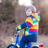 Scherzi il ragazzo in casco di sicurezza e bici variopinta di guida dell'impermeabile, outd Immagine Stock