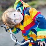 Scherzi il ragazzo in casco di sicurezza e bici variopinta di guida dell'impermeabile, outd Immagine Stock Libera da Diritti