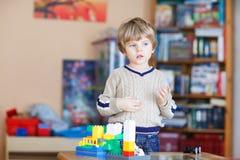 Scherzi il ragazzo che gioca con i lotti dei blocchi di plastica variopinti dell'interno Fotografie Stock Libere da Diritti