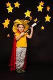 Scherzi il ragazzo che gioca l'osservatore del cielo con un telescopio Fotografia Stock