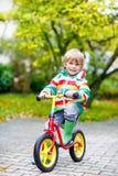 Scherzi il ragazzo che guida sulla bicicletta il giorno piovoso all'aperto Fotografia Stock Libera da Diritti