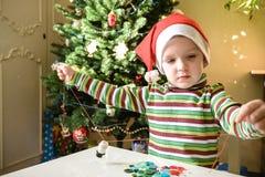 Scherzi il ragazzo del bambino che fa dalle decorazioni di natale delle mani Immagini Stock
