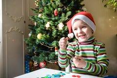 Scherzi il ragazzo del bambino che fa dalle decorazioni di natale delle mani Fotografie Stock Libere da Diritti