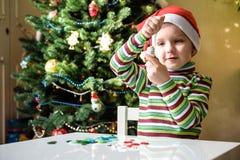 Scherzi il ragazzo del bambino che fa dalle decorazioni di natale delle mani Fotografia Stock Libera da Diritti