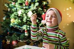 Scherzi il ragazzo del bambino che fa dalle decorazioni di natale delle mani Fotografia Stock
