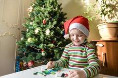 Scherzi il ragazzo del bambino che fa dalle decorazioni di natale delle mani Immagine Stock