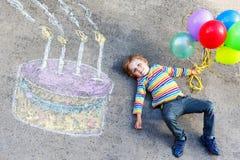 Scherzi il ragazzo divertendosi con il disegno variopinto della torta di compleanno con chal Immagini Stock