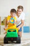 Scherzi il ragazzo ed il papà che giocano con il tronco del giocattolo Immagine Stock Libera da Diritti