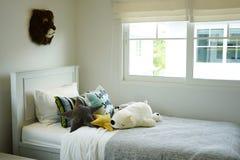 Scherzi la camera da letto del ` s con i cuscini variopinti sul letto con le bambole Fotografie Stock Libere da Diritti
