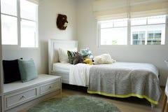Scherzi la camera da letto del ` s con i cuscini variopinti sul letto con le bambole Immagini Stock