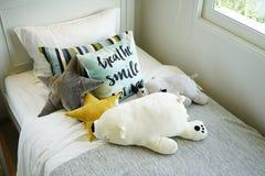 Scherzi la camera da letto del ` s con i cuscini variopinti sul letto con le bambole Fotografia Stock