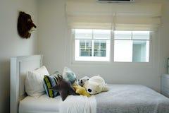 Scherzi la camera da letto del ` s con i cuscini variopinti sul letto con le bambole Fotografia Stock Libera da Diritti