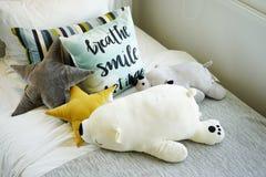 Scherzi la camera da letto del ` s con i cuscini variopinti sul letto con le bambole Immagine Stock Libera da Diritti