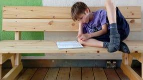 Scherzi la lettura del libro su un banco di legno leggero immagini stock