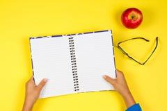 Scherzi la mano con il taccuino aperto, i vetri e la mela rossa su fondo giallo Fotografia Stock