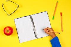 Scherzi la mano con il taccuino aperto, la penna, i vetri e la mela fresca su fondo giallo Immagine Stock