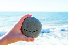 Scherzi la mano del ` s che tiene una pietra con il fronte sorridente accanto al mare nel giorno soleggiato immagini stock libere da diritti