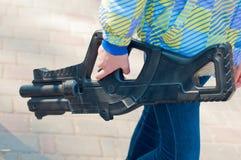 Scherzi la pistola del giocattolo della tenuta in sua mano sul pomeriggio soleggiato Immagine Stock
