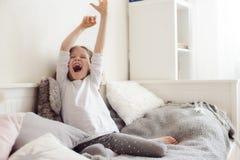Scherzi la ragazza che allunga nella sua stanza, sedentesi sul letto di mattina Fotografie Stock