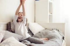 Scherzi la ragazza che allunga nella sua stanza, sedentesi sul letto di mattina Fotografia Stock Libera da Diritti