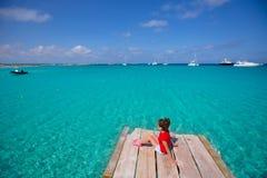 Scherzi la ragazza che esamina il mar Mediterraneo tropicale dal pilastro di legno Fotografia Stock