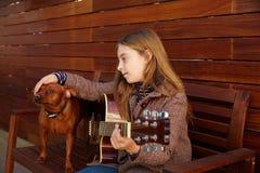 Scherzi la ragazza che gioca la chitarra con il cane ed il berretto dell'inverno Fotografia Stock Libera da Diritti