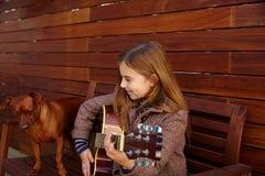 Scherzi la ragazza che gioca la chitarra con il cane ed il berretto dell'inverno Fotografia Stock