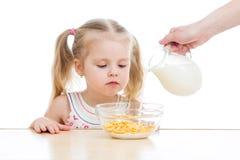 Ragazza del bambino che mangia i fiocchi di mais con latte Fotografia Stock