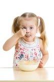 Ragazza del bambino che mangia i fiocchi di mais con latte Fotografie Stock