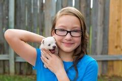 Scherzi la ragazza con il gioco della chihuahua dell'animale domestico del cucciolo felice Fotografia Stock