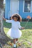 Scherzi la ragazza con la bacchetta magica della foglia di autunno all'aperto Immagini Stock Libere da Diritti