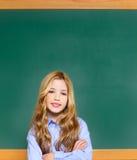 Scherzi la ragazza dell'allievo sulla lavagna verde del banco Immagini Stock Libere da Diritti