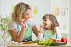 Scherzi la ragazza e la madre che mangiano le verdure sane dell'alimento Fotografia Stock