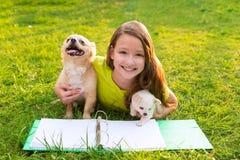 Scherzi la ragazza ed il cucciolo di cane a compito che si trova nel prato inglese Immagine Stock Libera da Diritti