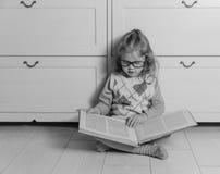 Scherzi la ragazza in vetri con un libro che si siede sulla lettura del pavimento Fotografia Stock