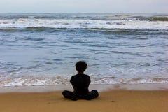 Scherzi la seduta isolata su una vista della spiaggia da dietro, sul concetto di solitudine e da solo fotografie stock libere da diritti